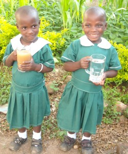 Twins Lydia and Barbara are holding two glasses of water. The first is the water the used to drink, dirty and filled with disease. The second the clean water of the Jesse well built in their village of Busolo, Uganda.