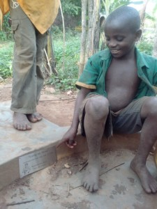 This boy is sitting on the concrete of the borehole and pointing at the plaque .